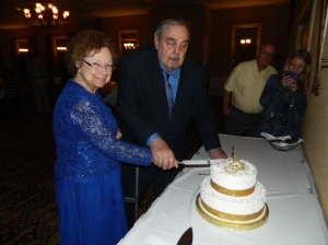 50 years later, Mom and Dad re-enacting the cake cutting at their anniversary party